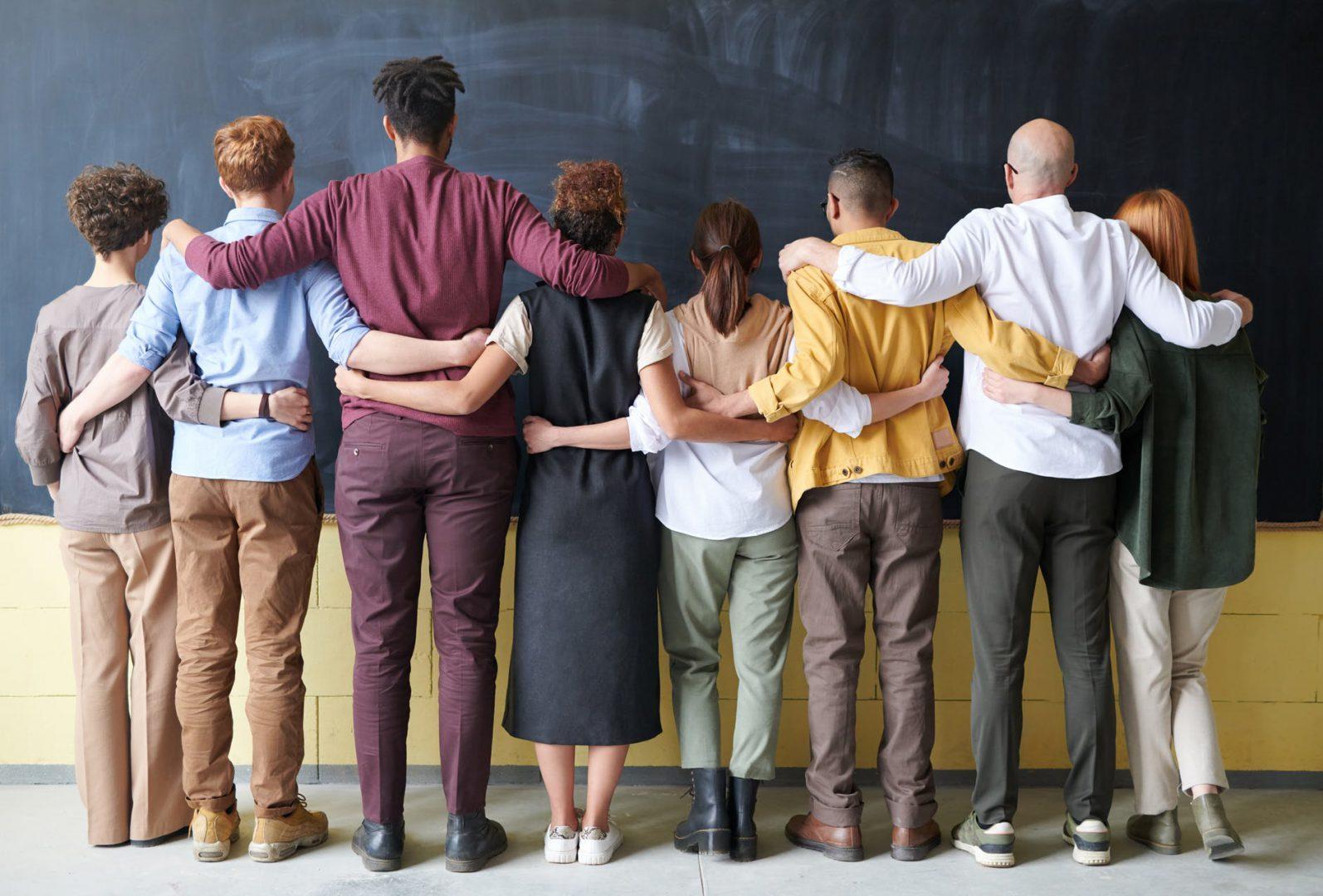 Obraz przedstawia grupkę osób, które stojąc obrócone plecami do obiektywu trzymają się wspólnie