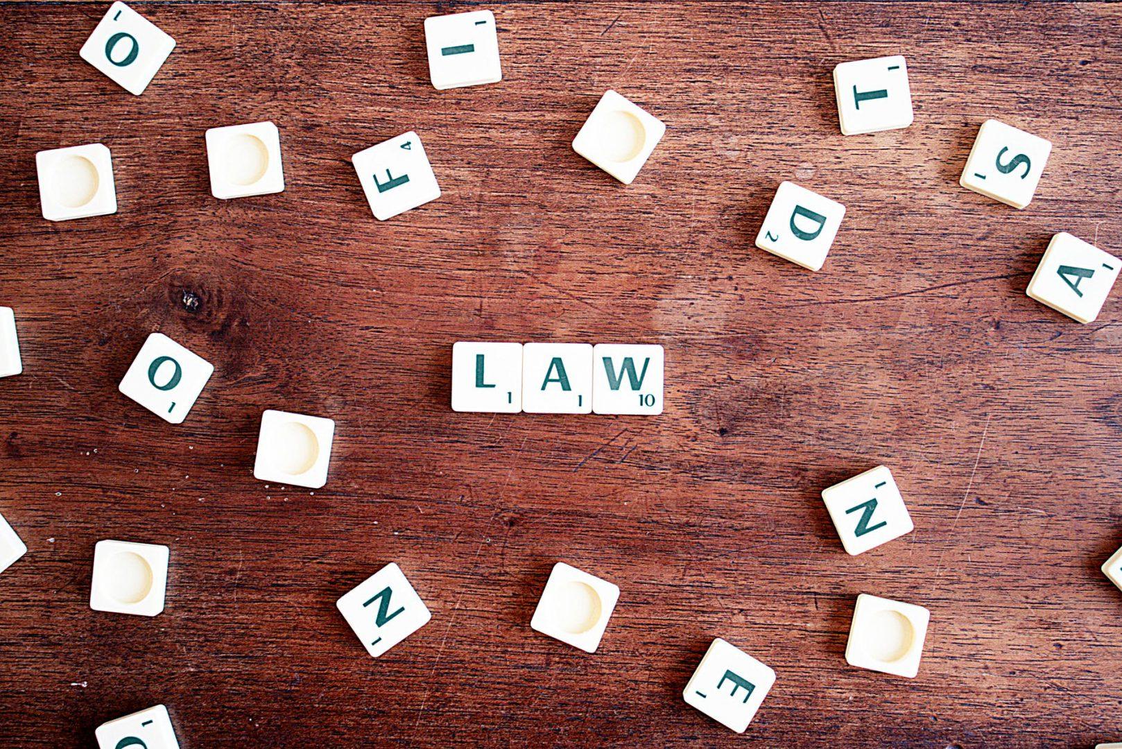 Obraz przedstawia napis law w języku angielskim, który ułożony jest z białych klocków z zielonymi literkami