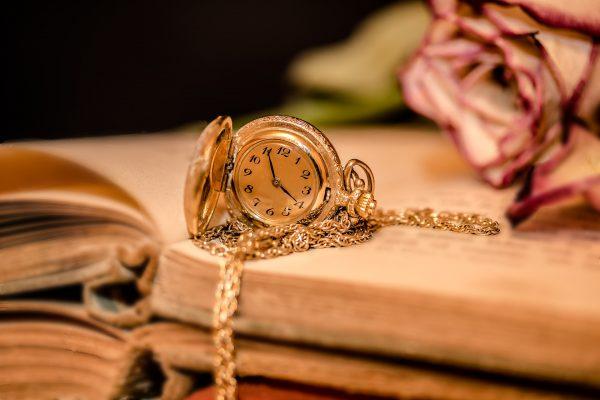 Zegarek leżący na książce z różą w tle