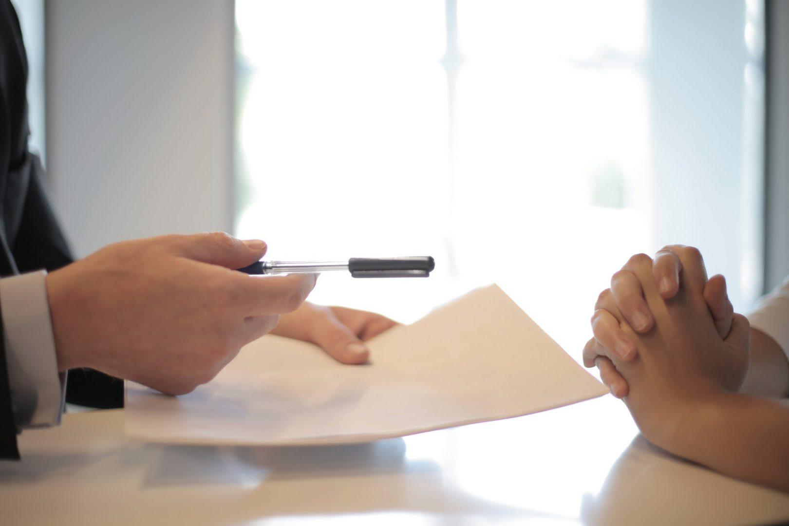 Dwóch ludzi z kartką papieru oraz długopisem