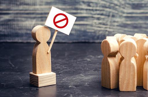 Drewniany ludzik z tabliczką ze znakiem zakazu